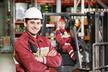 chofer: empleado de almac�n en frente de la carretilla elevadora Foto de archivo
