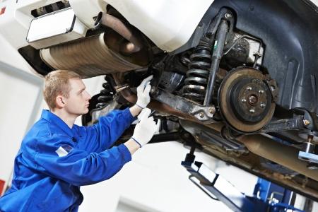 mecanico automotriz: mecánico de automóviles en el trabajo de reparación de automóviles suspensión Foto de archivo