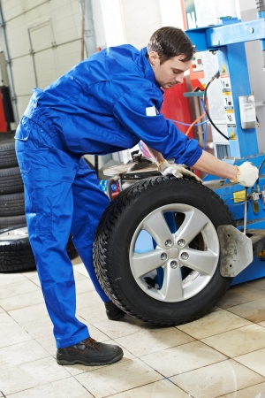 tire fitting: repairman mechanic at wheel replacement Stock Photo