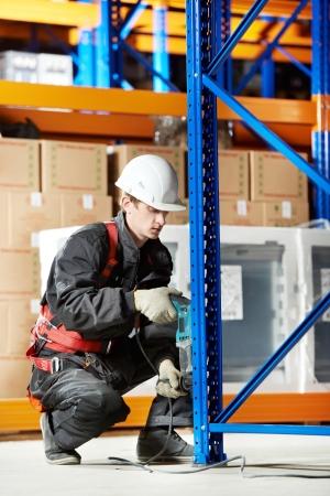 assemblage: warehouse worker installing rack arrangement Stock Photo