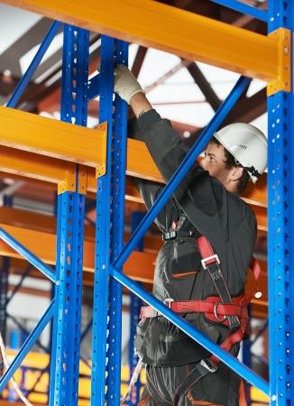 rack arrangement: warehouse worker installing rack arrangement Stock Photo