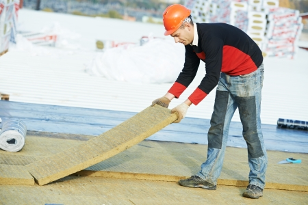 site preparation: roofer worker installing roof insulation material Stock Photo