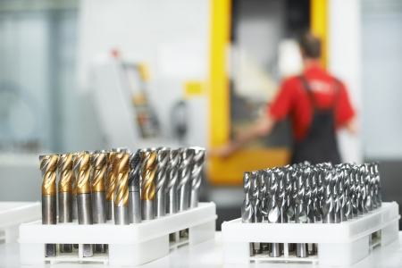 cnc machine: industrial cutting tools in front of cnc milling machine center in tool workshop manufacturing