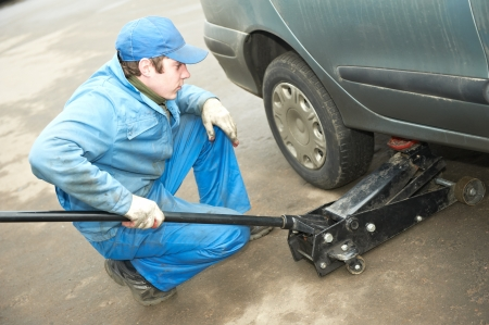 machanic repairman at tyre fitting with car jack Stock Photo - 18123809