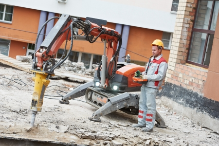 builder worker operating demolition machine photo