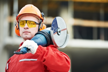 protective workwear: builder worker at construction site Stock Photo