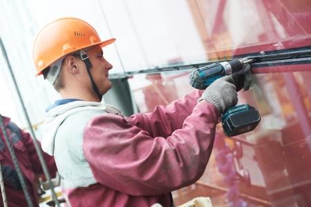 double glazing: worker installing glass window on building