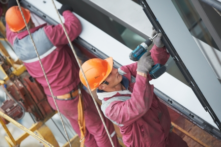 double glazing: workers installing glass window on building