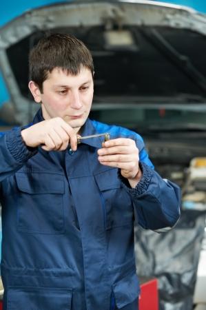car mechanic inspecting engine sparking plug photo
