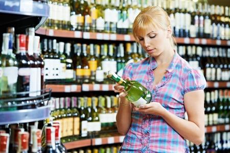 jovenes tomando alcohol: mujer elegir y comprar vino en el supermercado Foto de archivo
