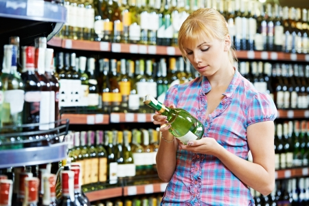 people buying: woman choosing and shopping wine at supermarket Stock Photo