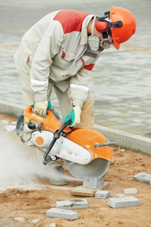 millwright: builder worker cutting curb with disc saw Stock Photo