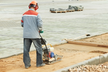 site preparation: concrete worker work with compactor Stock Photo