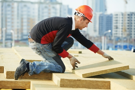 insulating: roofer worker installing roof insulation material Stock Photo
