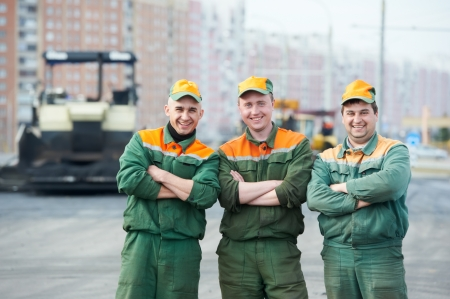 construction crew: three asphalt road workers Stock Photo