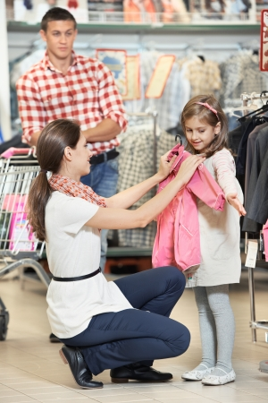 choosing selecting: woman and little girl shopping clothes