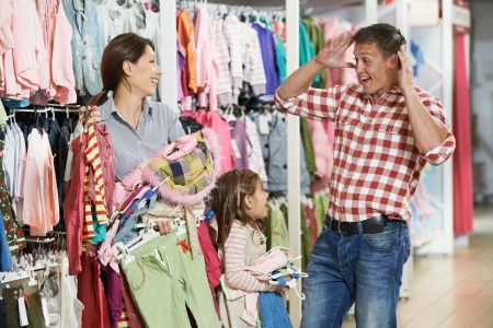 choosing clothes: woman and little girl shopping clothes