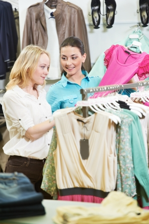 two Young women at apparel clothes shopping photo