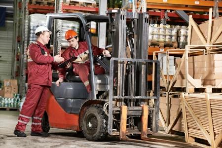 carretillas almacen: trabajadores del almacén en frente de la carretilla elevadora Foto de archivo