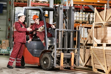 warehouse workers in front of forklift photo