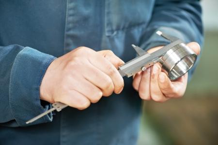 vernier caliper: worker measuring detail with caliper