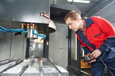 man machine: worker operating CNC machine center Stock Photo