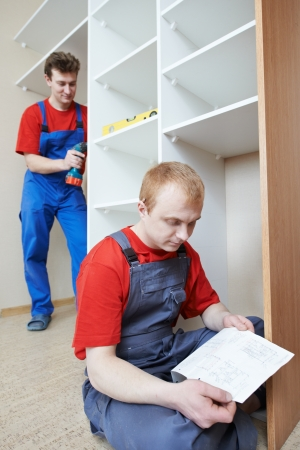 Wardrobe joiners at installation work photo