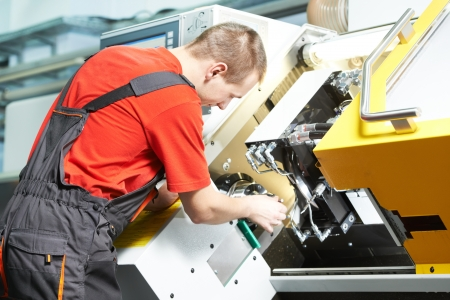 fettler: worker operating CNC machine center Stock Photo