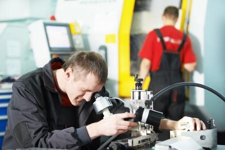 control de calidad: trabajador comprueba la herramienta con dispositivo �ptico Foto de archivo