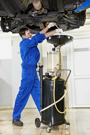 replacing: car mechanic replacing oil from motor engine