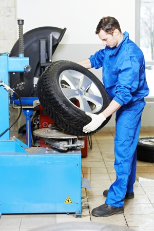 tire fitting: mechanic at auto wheel tyre changer