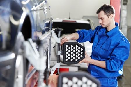 alineaci�n: mec�nico de autom�viles en el trabajo de alineaci�n de ruedas con sensor Foto de archivo