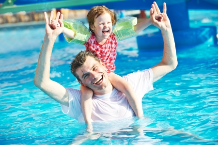 Father and child in resort swimming pool photo