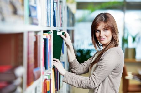 choose university: young student selecting book in library