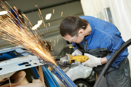 repairman grinding metal body car photo
