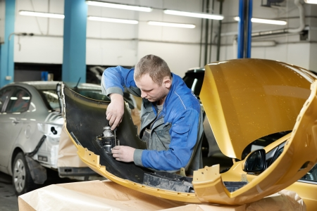 car manufacturing: repairman grinding metal body car