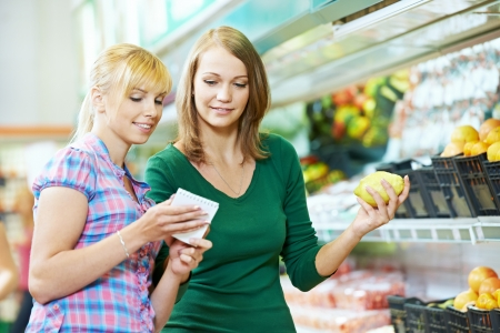 Two women at supermarket fruits shopping photo