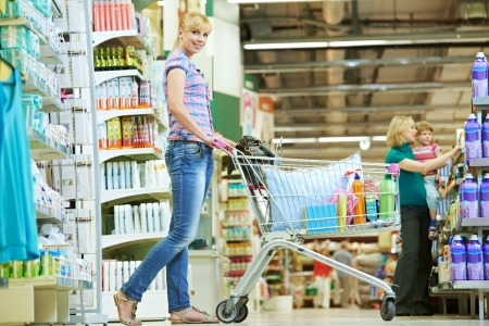 household goods: Shopping woman with cart at supermarket