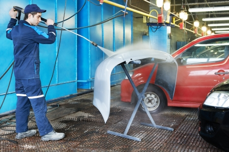 worker cleaning car bumper with pressured water photo