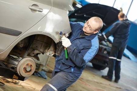 repair man: auto repair man flatten metal body car Stock Photo