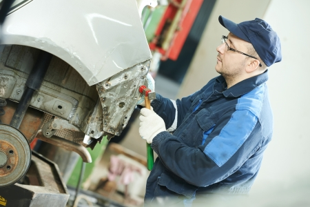 flatten: auto repair man flatten metal body car Stock Photo