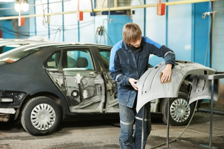 bodywork: repairman sanding plastic car bumper Stock Photo
