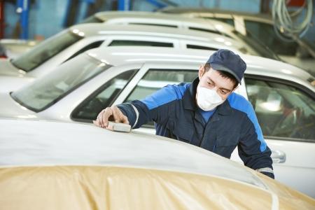 sander: repairman sanding automobile roof