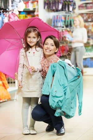 woman and little girl shopping clothes photo