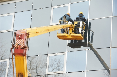 glazing: workers installing glass window on building