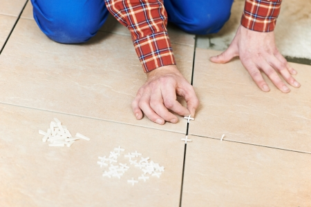 tile flooring: tiler hands at home renovation work Stock Photo