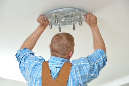 Electrician at wiring work in home photo
