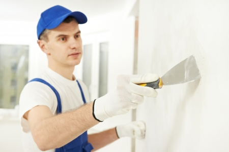putty: Plasterer with putty knife at wall filling Stock Photo