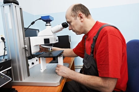 worker checking probe with industrial microscope photo