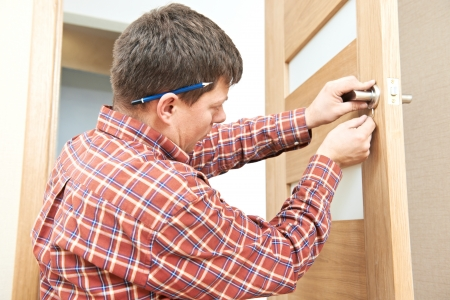 occupations and work: carpenter at door lock installation Stock Photo